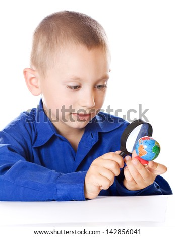 Schoolboy with a magnifying glass carefully consider Globe - stock photo