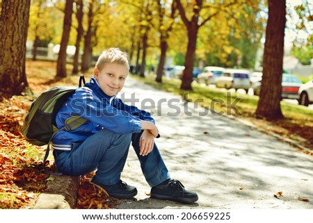 schoolboy with backpack after school in park