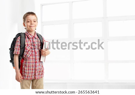 Schoolboy with backpack at school. Child at classroom - stock photo