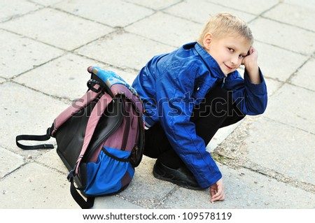 schoolboy with backpack does not want to go back to school - stock photo