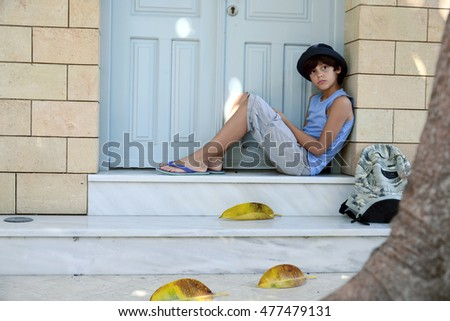 Schoolboy  with blue straw hat under a large tree