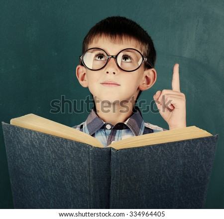 Schoolboy with book at the blackboard in classroom - stock photo