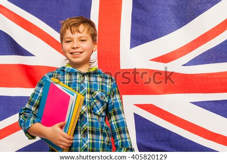 Schoolboy with textbooks against English flag - stock photo
