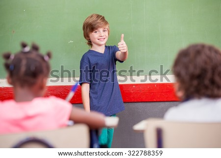 Schoolboy with thumb up during a lesson.
