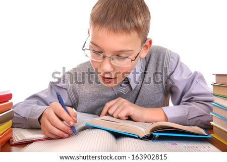 Schoolboy writing at the School Desk on the white background - stock photo