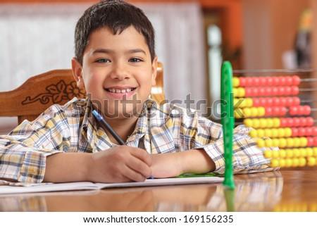 Schoolboy writing homework - stock photo