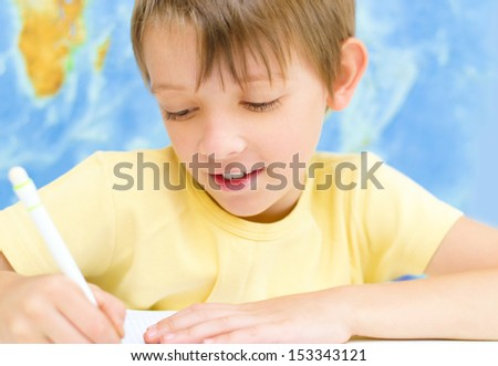 schoolboy writing in his workbook using a pen in front of world map - stock photo
