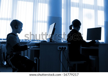 Schoolboys at school work behind computers - stock photo