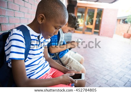 Schoolboys using mobile phones while sitting at corridor in school - stock photo