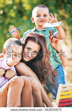 Schoolboys with their mother smiling in park, waving and making finger signs to the camera. - stock photo