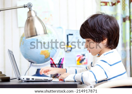 schoolchild at a desk working on a computer - stock photo
