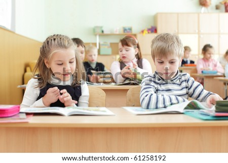 Schoolchild behind desks at school - stock photo