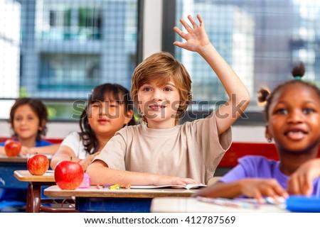 Schoolchild raising hand in classroom. Education concept. - stock photo