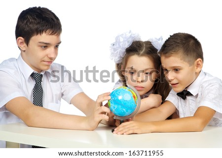 schoolchildren and the globe, studio, isolated, white background.