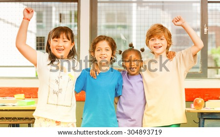 Schoolchildren embracing happy. Multi cultural racial classroom. - stock photo