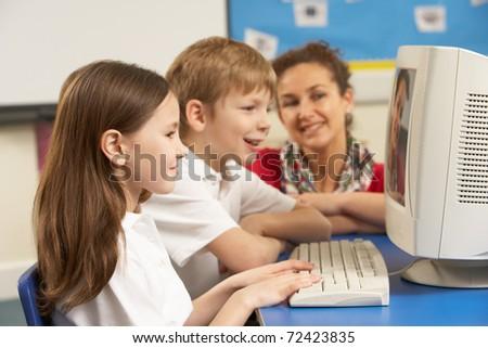 Schoolchildren In IT Class Using Computer with teacher - stock photo