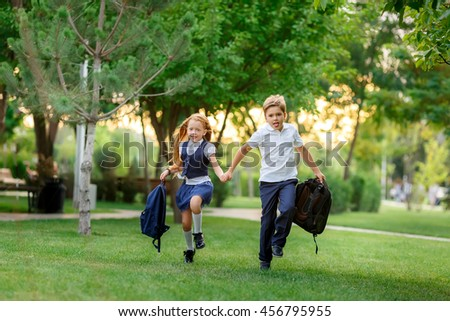 Schoolchildren running in the park after school. waving backpacks. September 1