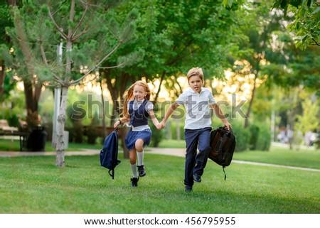 Schoolchildren running in the park after school. waving backpacks. September 1 - stock photo