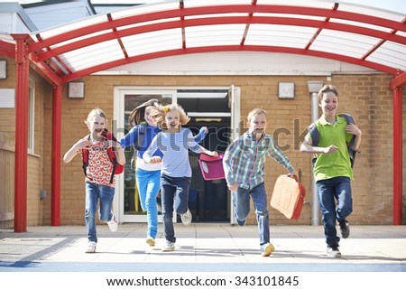 Schoolchildren Running Into Playground At End Of Class - stock photo