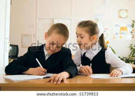 schoolchildren sitting in classroom and writing