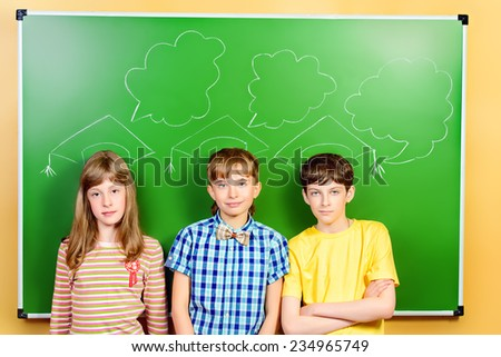 Schoolchildren stand at the blackboard in the classroom. Educational concept. New idea. - stock photo