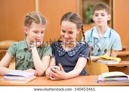 schoolchildren using mobile phone at lesson break - stock photo