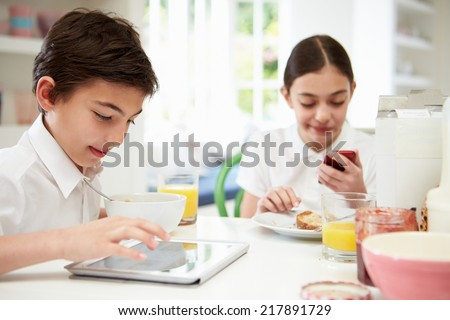 Schoolchildren With Digital Tablet And Mobile At Breakfast - stock photo