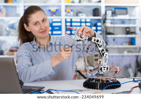 schoolgirl adjusts the robot arm model, girl in a robotics laboratory - stock photo