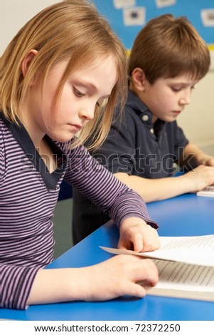 Schoolgirl And Schoolboy Studying In Classroom - stock photo