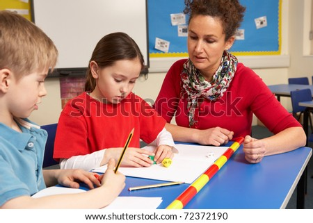 Schoolgirl And Schoolboy Studying In Classroom With Teacher - stock photo