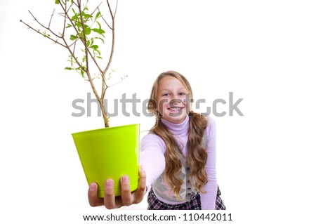 Schoolgirl and the pomegranate tree in the green pot - stock photo