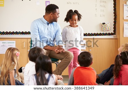 Schoolgirl at the front of elementary class with teacher - stock photo
