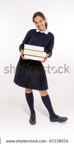 Schoolgirl carrying three heavy books - stock photo