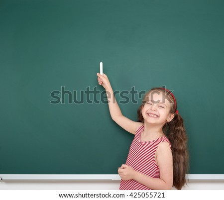 schoolgirl child in red striped dress point and drawing on green chalkboard background, summer school vacation concept - stock photo
