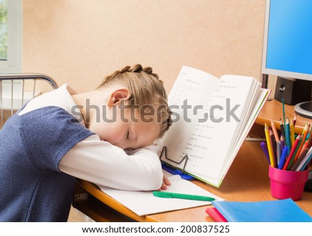 Schoolgirl dreaming on books sitting at the table - stock photo