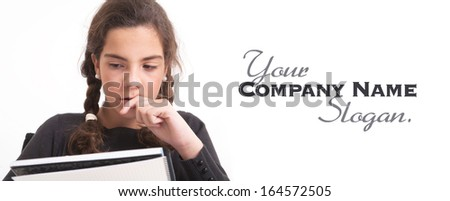 Schoolgirl holding a notebook with a concentrated expression  - stock photo