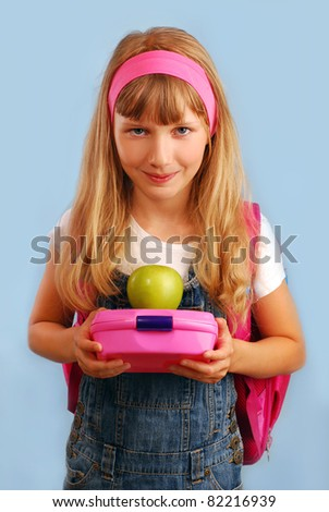 schoolgirl  holding lunch box and apple  going to eat - stock photo