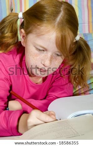 Schoolgirl is making homework - stock photo