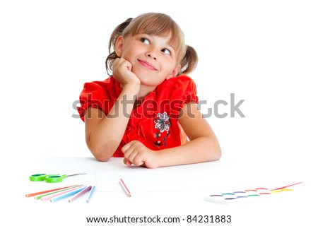 Schoolgirl is sitting at table with pencils, paints and scissors isolated - stock photo