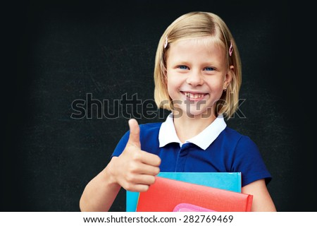 Schoolgirl is standing next to blackboard and holds in hands textbooks. She shows hand that everything is fine. - stock photo