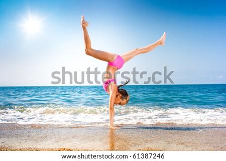 schoolgirl making gymnastics on seashore - stock photo