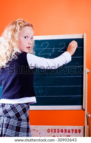 schoolgirl making homework at a blackboard