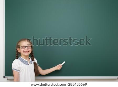 Schoolgirl near the school board - stock photo
