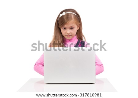 schoolgirl on a white background in surprise looks in the laptop, picture with depth of field and artistic blur - stock photo