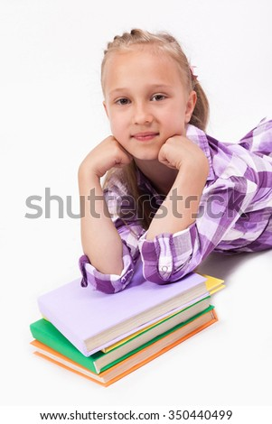schoolgirl on a white background lying on his belly resting on the book. - stock photo