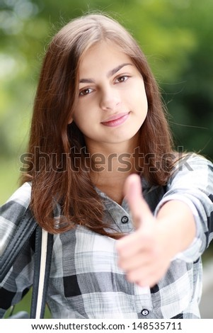 Schoolgirl Outdoor with book bag shows thumb up okey. Back to School - stock photo