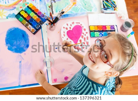 Schoolgirl painting with water color - top view - stock photo