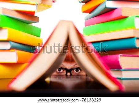 schoolgirl peeking behind books,  funny concept, isolated on white - stock photo