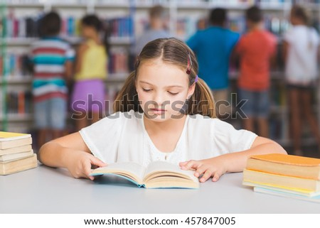 Schoolgirl reading book in library at elementary school