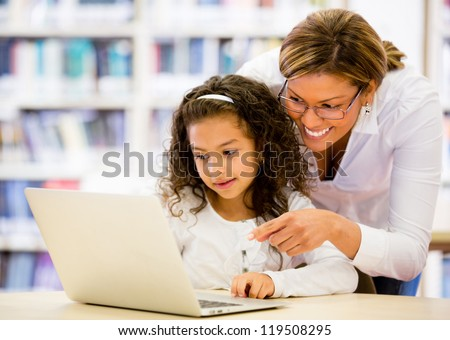 Schoolgirl researching online with the guidance of her teacher - stock photo